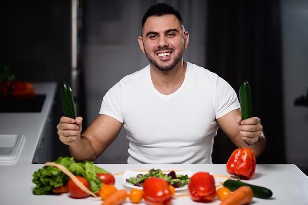 Homem bonito para comer comida vegetariana saudável em casa.