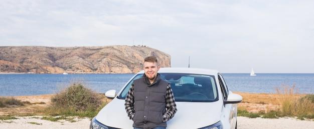 Homem bonito parado na frente de um carro branco