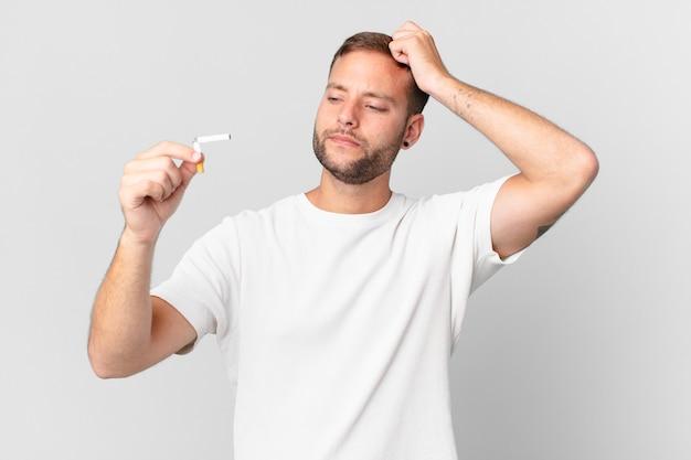 Homem bonito parando de fumar com um charuto quebrado