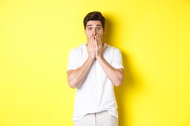 Homem bonito parecendo chocado e sem palavras, segurando as mãos na boca, em pé sobre um fundo amarelo.