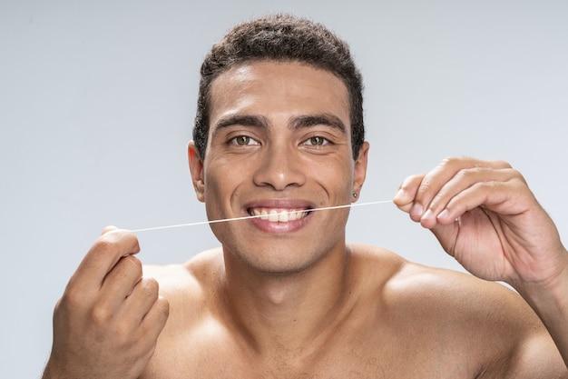 Homem bonito passando fio dental nos dentes com um sorriso cheio de dentes