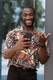 Homem bonito passando um tempo ao ar livre usando um smartphone moderno