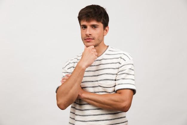 Homem bonito pensando em pé isolado na parede branca.