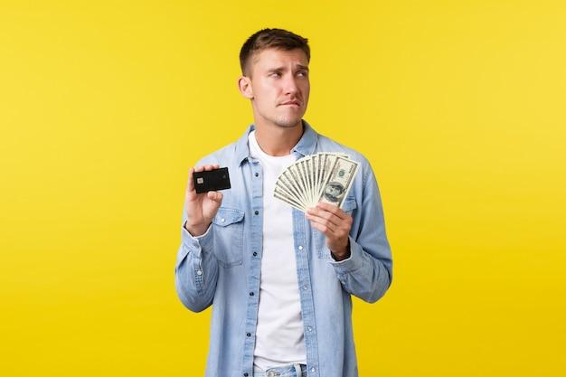 Homem bonito pensativo e indeciso, preocupado em roupas casuais, parecendo perplexo e mordendo o lábio, tentando comprar algo caro, mostrando um cartão de crédito com dinheiro.