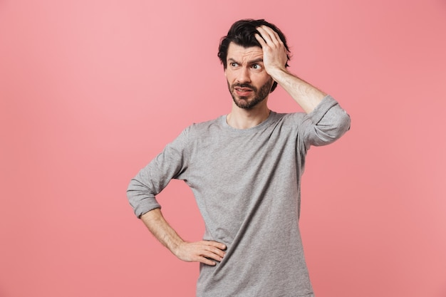 Homem bonito, pensativo, jovem, barbudo, morena, vestindo um suéter em pé rosa