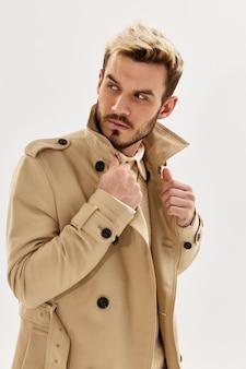 Homem bonito penteado na moda bege casaco olhar lateral isolado fundo