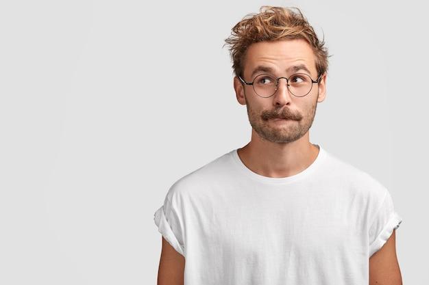 Homem bonito perplexo com bigode, morde o lábio inferior e olha curiosamente para o lado, pensa em algo, vestido com uma camiseta branca casual, fica encostado na parede em branco