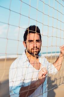 Homem bonito perto de rede de vôlei