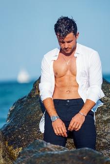 Homem bonito perto de uma rocha na praia