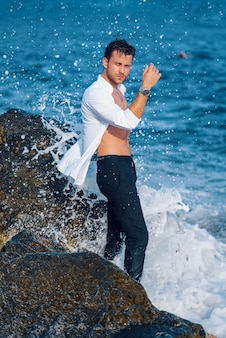 Homem bonito perto do mar na praia