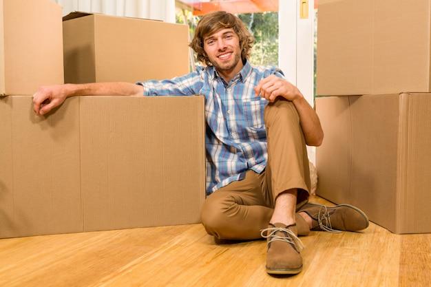 Homem bonito posando com caixas de mudança em sua nova casa