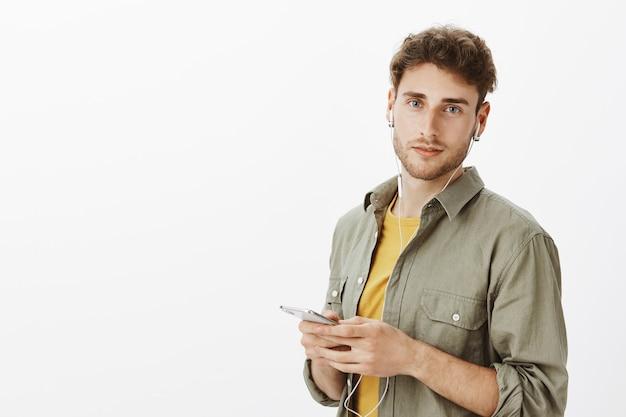 Homem bonito posando com smartphone no estúdio