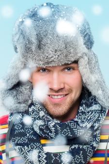 Homem bonito, posando durante a queda de neve