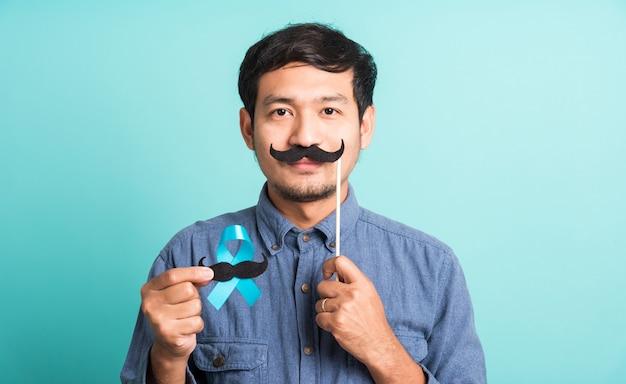 Homem bonito posando segurando uma fita azul claro e bigode