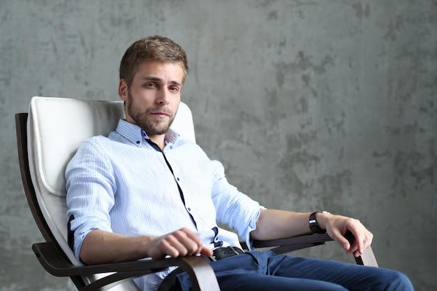 Homem bonito posando sentado na cadeira