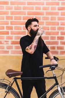 Homem bonito posar perto de seu ciclo contra a parede