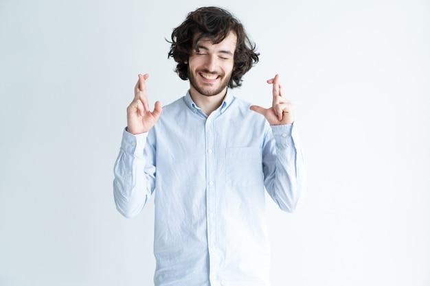 Homem bonito positivo, mostrando o gesto de dedos cruzados