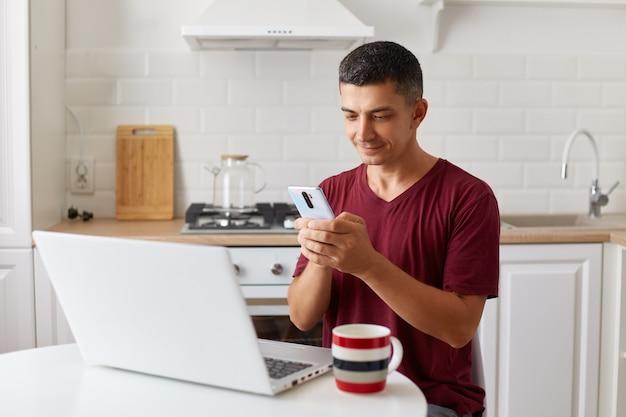 Homem bonito positivo trabalhando online em casa no laptop, usando o smartphone para verificar e-mails enquanto faz uma pausa para o trabalho freelance, olhando para a tela do dispositivo, digitando a mensagem.