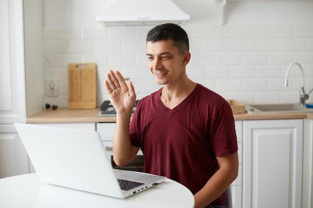 Homem bonito positivo vestindo trajes de estilo casual, sentado à mesa na cozinha em frente ao laptop, tendo uma videochamada, acenando com a mão para a câmera web, dizendo olá ou adeus.