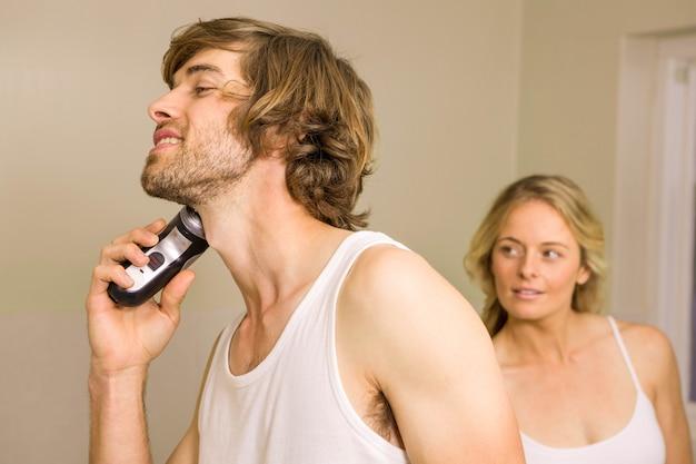 Homem bonito prestes a fazer a barba com a namorada para trás em casa