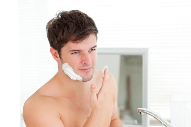Homem bonito pronto para fazer a barba no banheiro