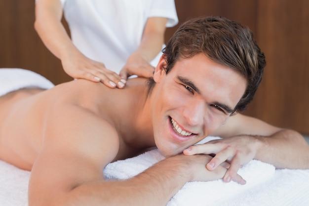 Homem bonito que recebe massagem no ombro no centro de spa