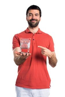 Homem bonito que segura um brinquedo do carrinho do supermercado