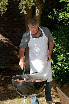 Homem bonito que tem um churrasco no jardim