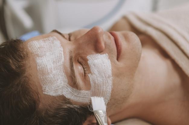 Homem bonito, recebendo tratamento de pele facial