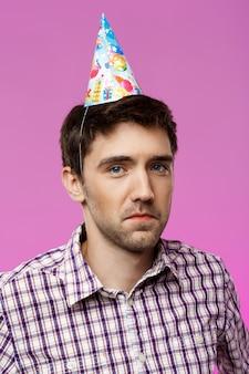 Homem bonito ressentido posando sobre parede roxa. festa de aniversário.