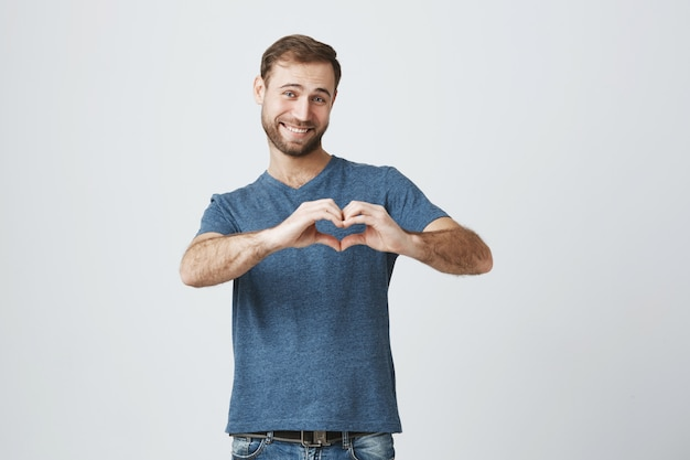 Homem bonito romântico sorrindo, mostra sinal de coração