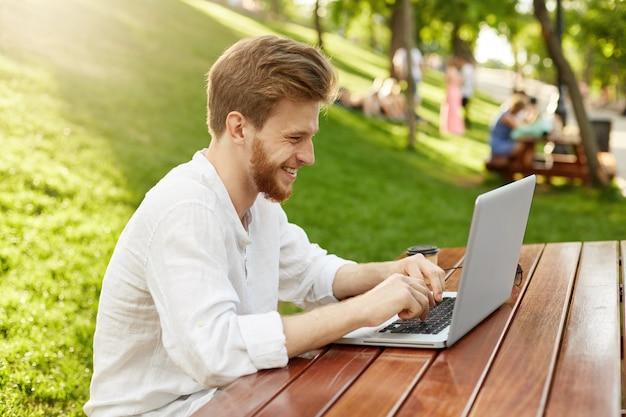 Homem bonito ruivo maduro com computador portátil no parque