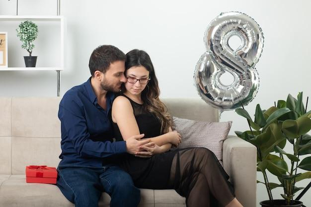 Homem bonito satisfeito, abraçando e olhando para uma bela jovem de óculos, sentada no sofá na sala de estar em março, dia internacional da mulher