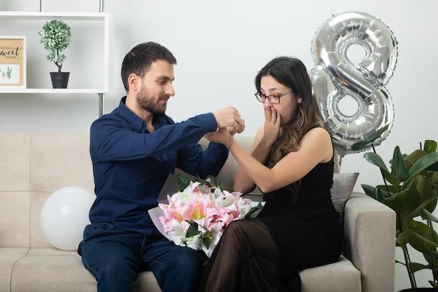 Homem bonito satisfeito colocando a pulseira na mão de uma jovem muito animada de óculos ópticos segurando um buquê de flores, sentada no sofá na sala de estar em março, dia internacional da mulher