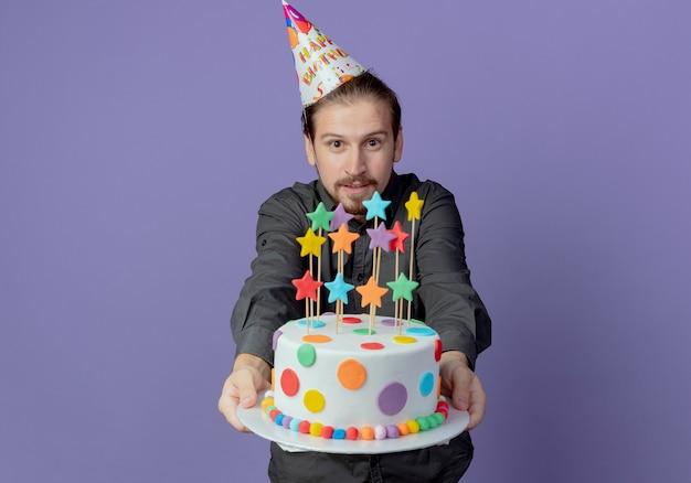 Homem bonito satisfeito com um chapéu de aniversário segurando um bolo de aniversário isolado na parede roxa