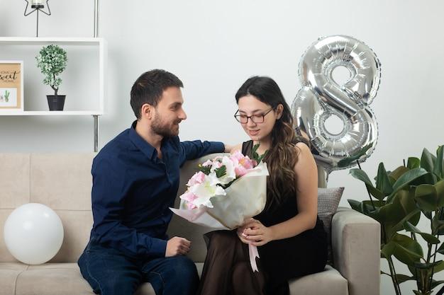 Homem bonito satisfeito olhando para uma bela jovem de óculos segurando um buquê de flores, sentada no sofá na sala de estar em março, dia internacional da mulher