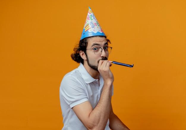 Homem bonito satisfeito usando óculos e boné de aniversário, soprando apito isolado em fundo laranja