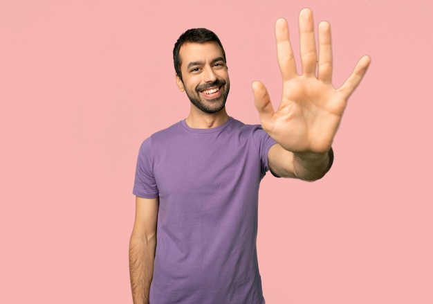 Homem bonito, saudando com a mão com uma expressão feliz no fundo rosa isolado