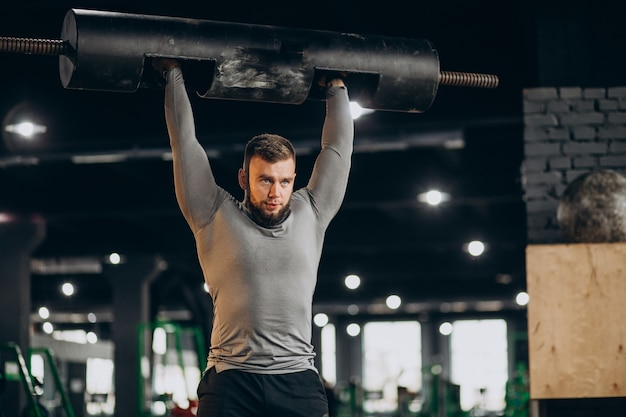 Homem bonito se exercitando na academia