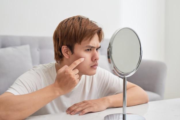 Homem bonito se olhando no espelho. espremendo espinha.
