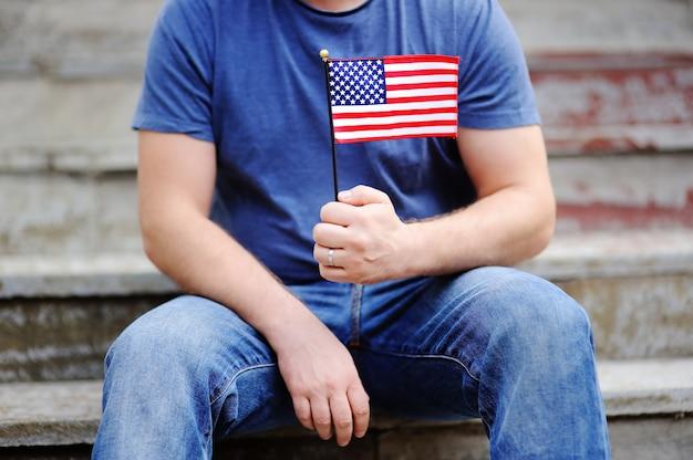 Homem bonito, segurando a bandeira americana. conceito do dia da independência.