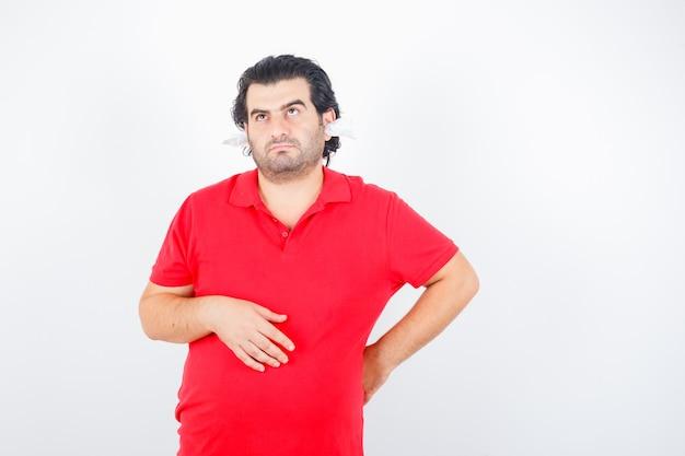 Homem bonito, segurando a mão atrás da cintura, pensando em algo, em pé com guardanapos nas orelhas em camiseta vermelha e olhando pensativo, vista frontal.