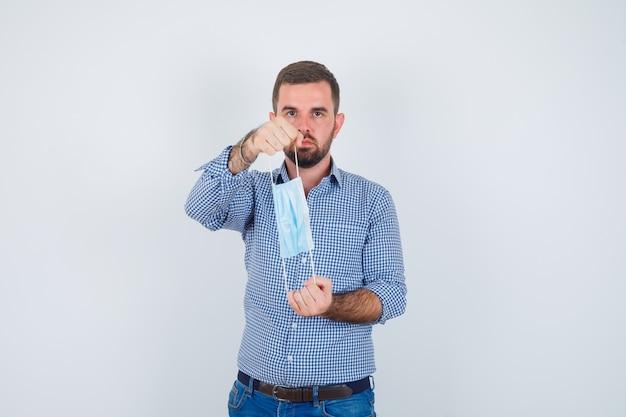 Homem bonito, segurando a máscara com as duas mãos na camisa, jeans e olhando sério, vista frontal.