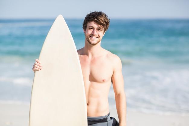Homem bonito, segurando a prancha de surf na praia