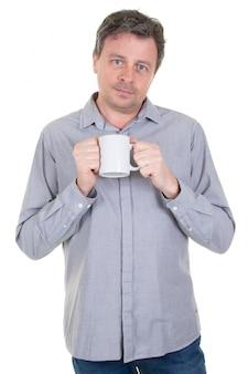 Homem bonito, segurando a xícara com chá de café com cara séria e caneca branca em branco na mão
