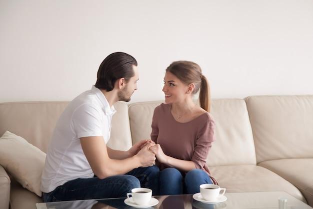 Homem bonito, segurando as mãos de mulher bonita sentada dentro de casa, proposta