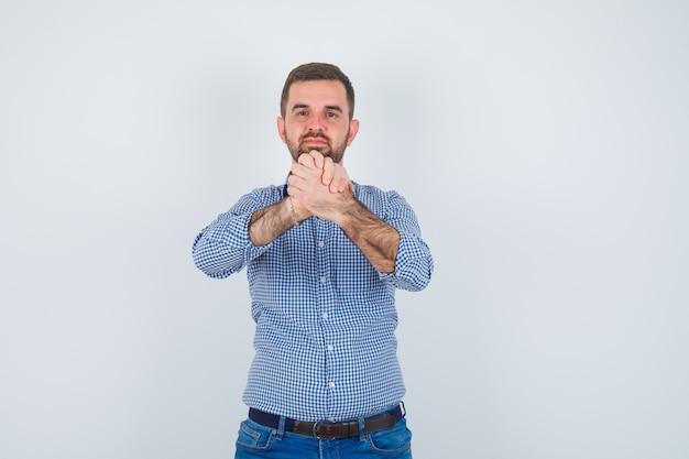 Homem bonito, segurando as mãos na camisa, jeans e olhando sério. vista frontal.