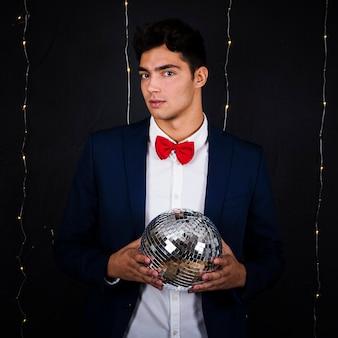 Homem bonito segurando bola de discoteca