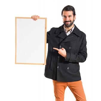 Homem bonito segurando cartaz vazio