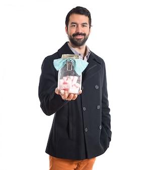 Homem bonito segurando frasco de vidro com doces por dentro